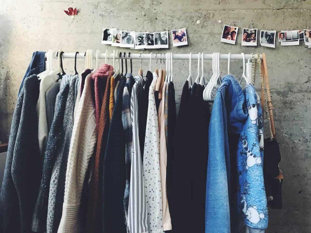 Second Hand Klamotten auf Kleiderständer mit Fotos an der Wand
