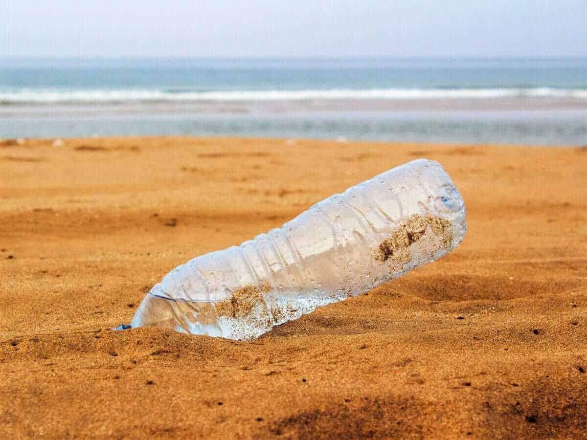 Plastik PET Flasche am Strand im Sand mit Meer im Hintergrund