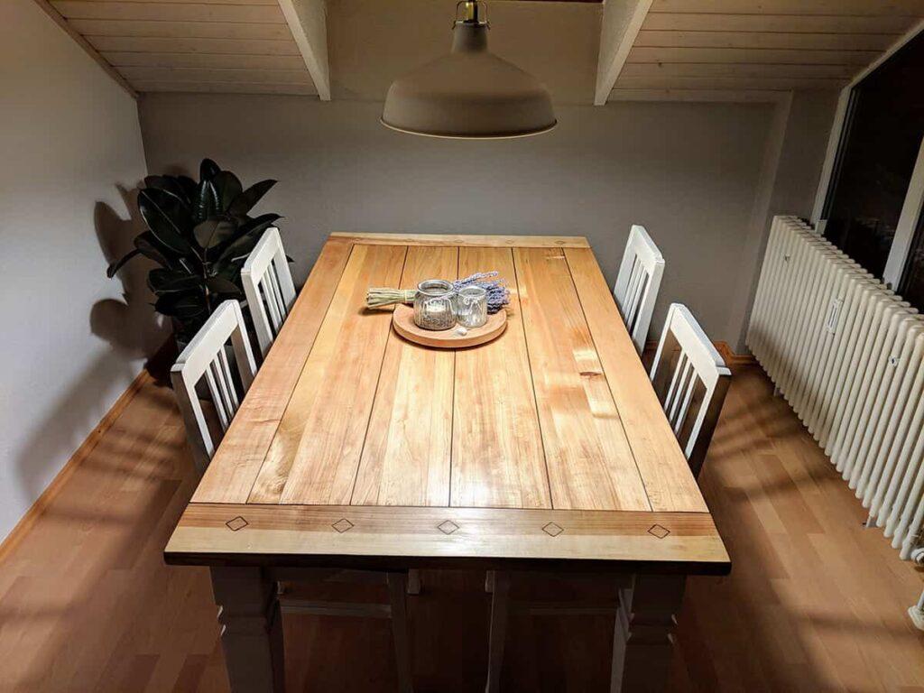wiederaufbereiteter alter Tisch mit Stühlen und Lampe