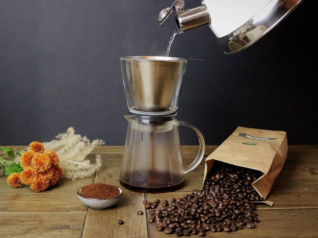Kaffe wird mit heißem Wasser aus Wasserkocher aufgebrüht