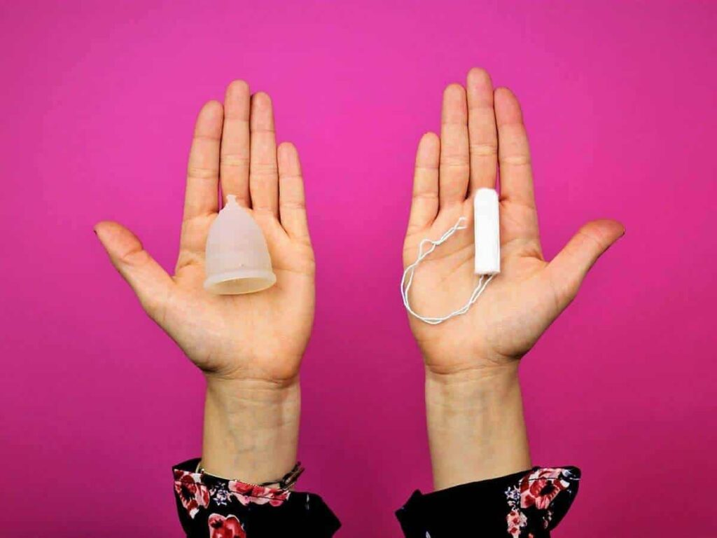 Menstruationstasse und Tampon auf Handfläche