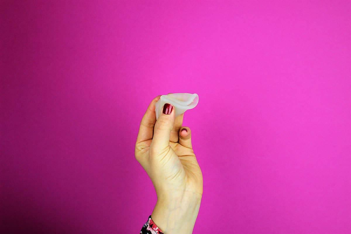 Menstruationstasse Dreieck Faltung in der Hand gehalten