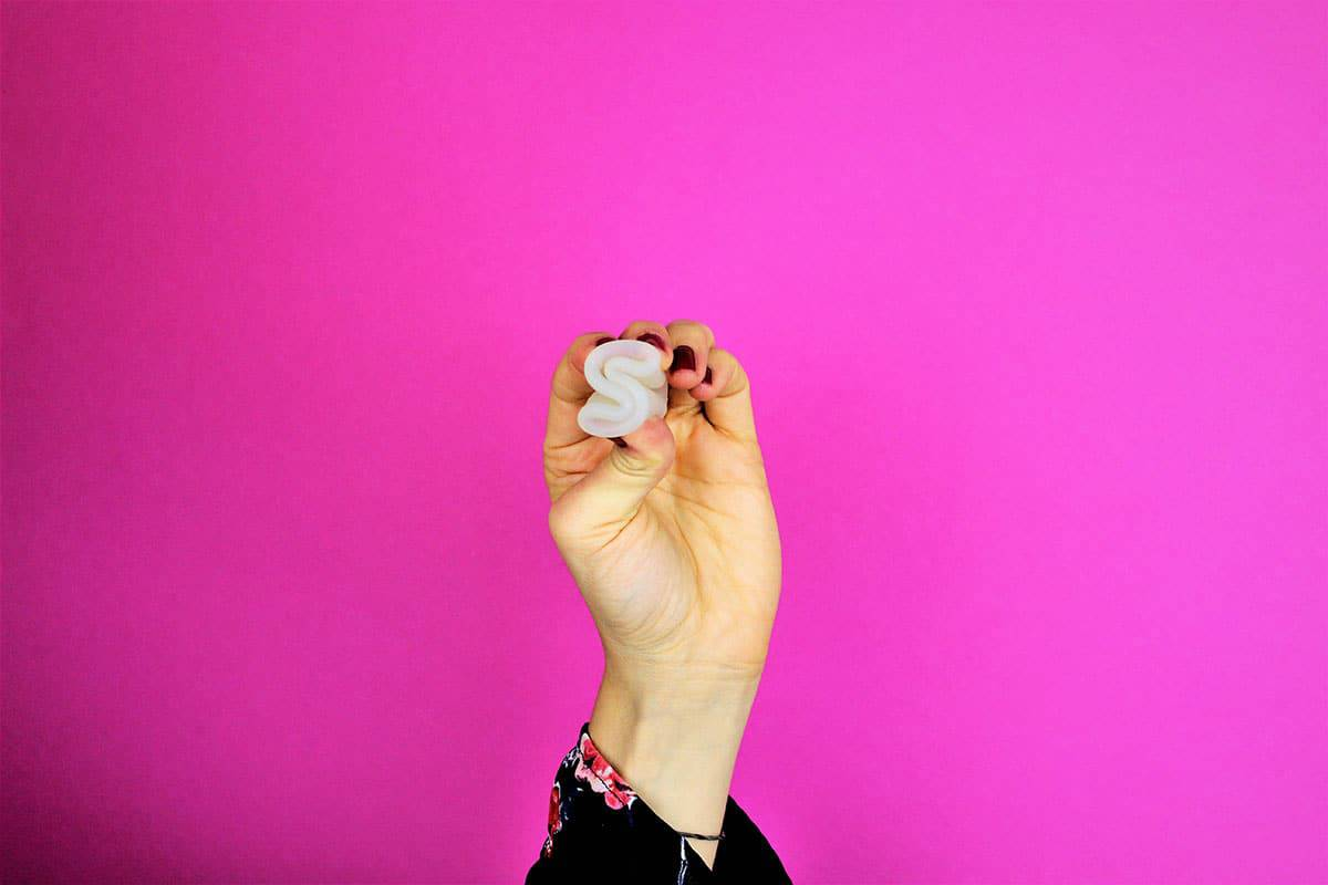Menstruationstasse in S gefaltet in Hand gehalten