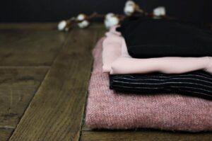 Zusammengelegte Kleidungsstücke auf Holztisch
