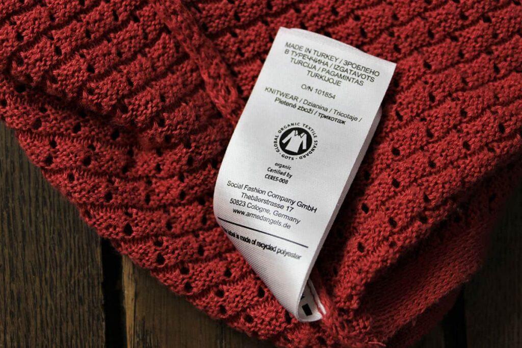 Zertifizierte Baumwolle mit Siegel und Etikett an rotem Pullover