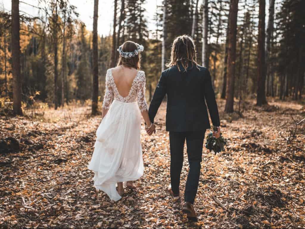 Boho Brautpaar von hinten Händchen haltend im Wald