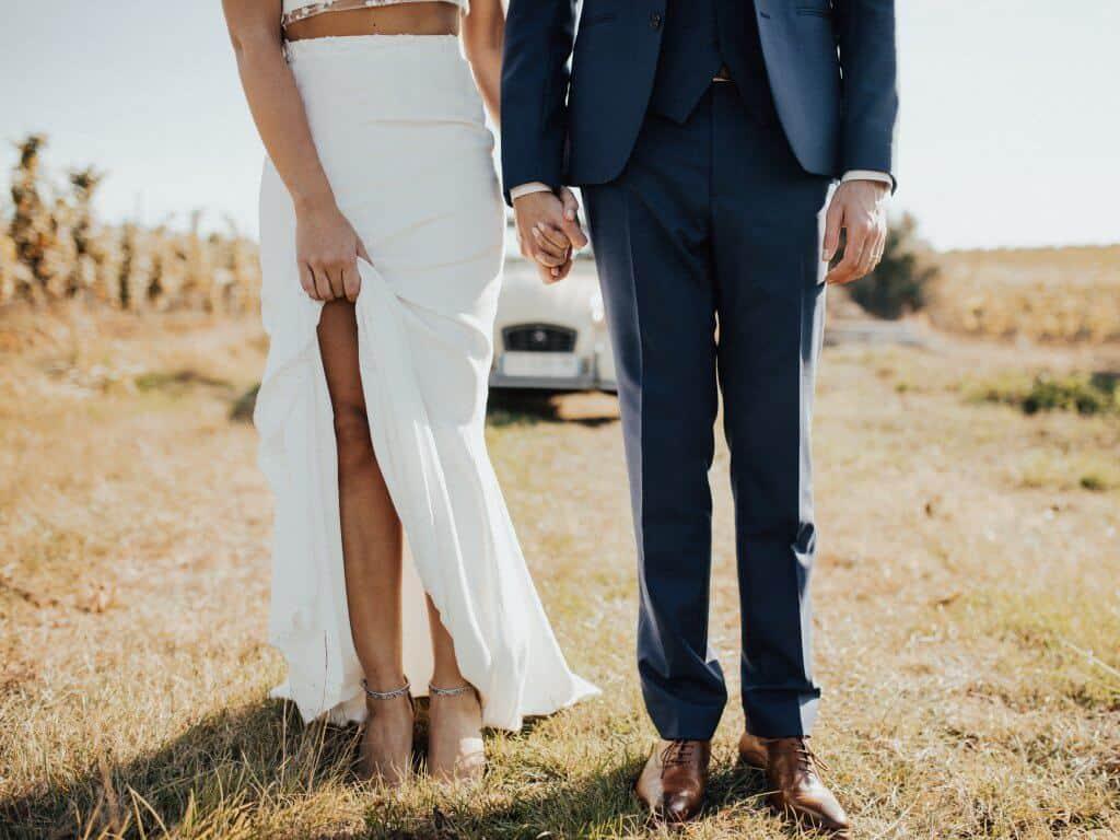 Braut in Brautkleid und Bräutigam auf Wiese mit Auto im Hintergrund