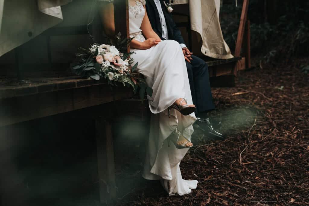 Braut und Bräutigam sitzen auf Holzsteg