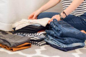 Aussortierte Kleidung auf Bett gestapelt neben sitzender Frau