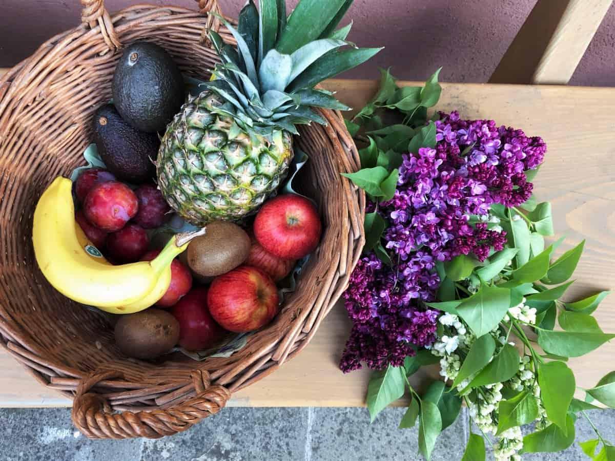 Bio Obst, Banane, Ananas und Äpfel in einem geflochtenen Korb