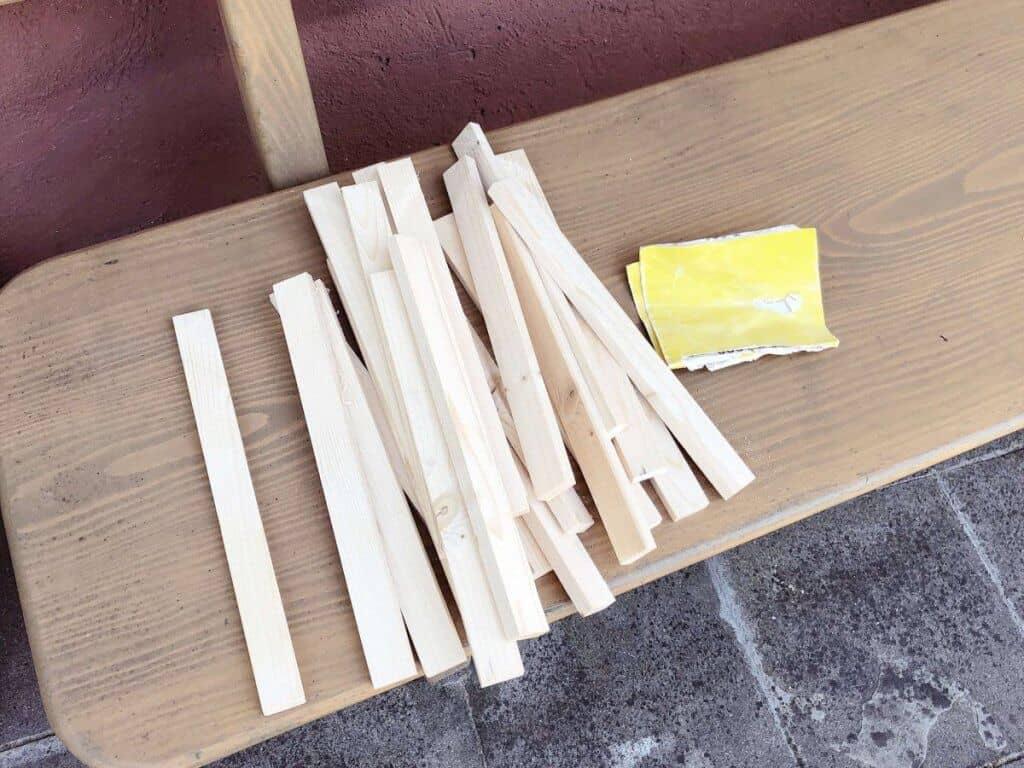Holzstäbe auf Holzbank mit Schleifpapier