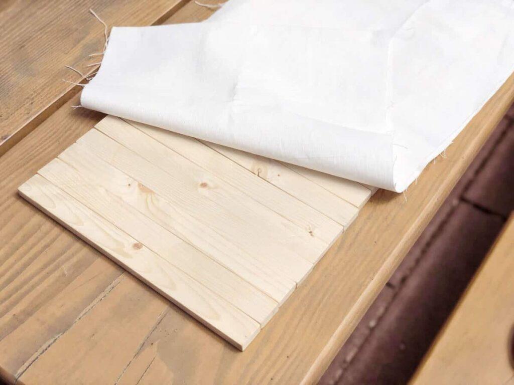 Holzstäbe mit Stoff auf Holztisch