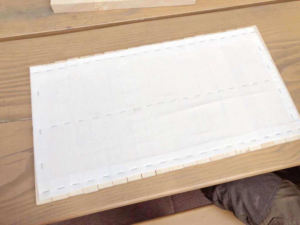 Stoff angetackert mit Tackernadeln auf Holzstäbchen