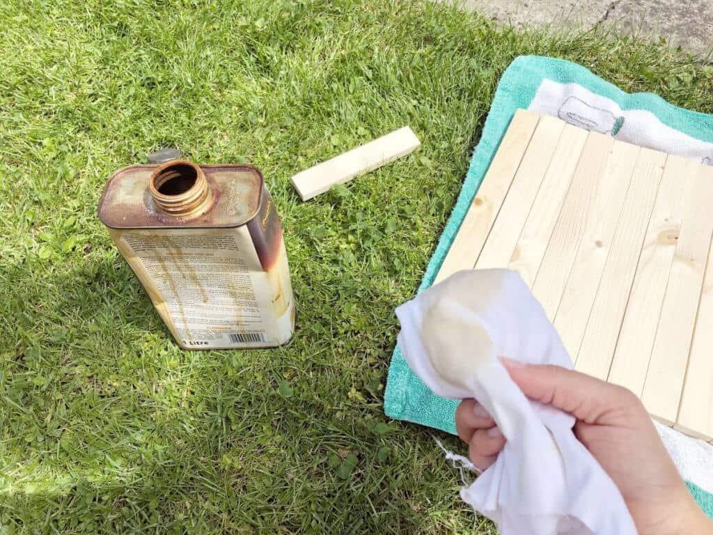 Dänisches Öl und Holz auf Rasen alter Lappen in der Hand