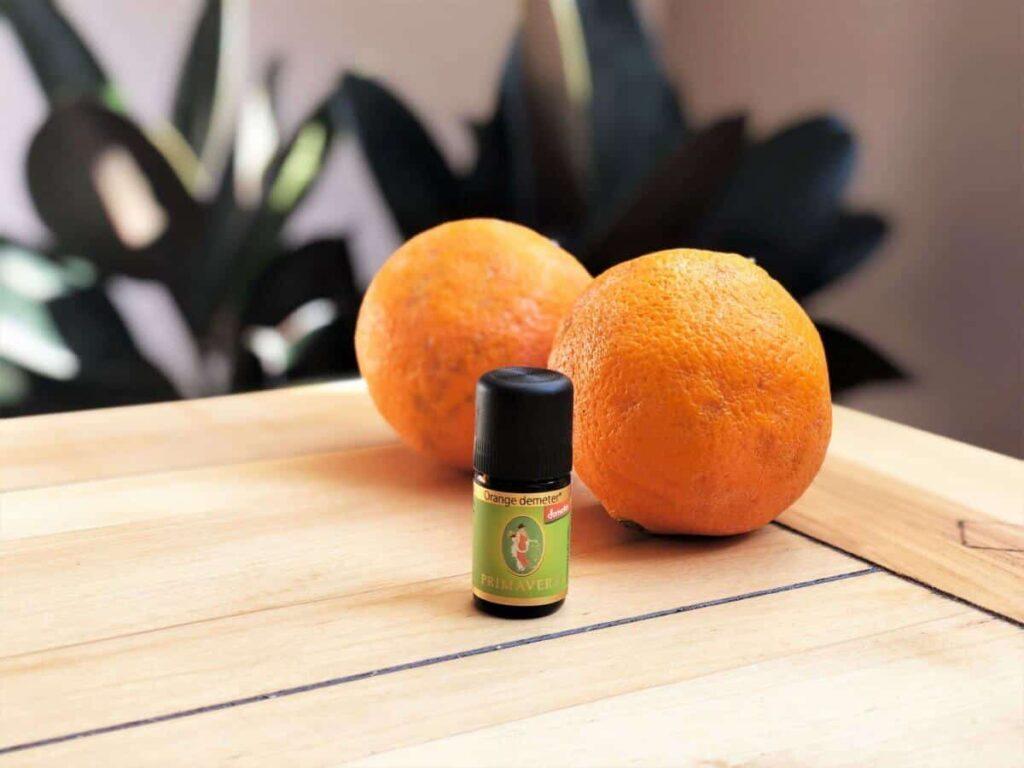 Orangenöl neben zwei Orangen auf Holztisch
