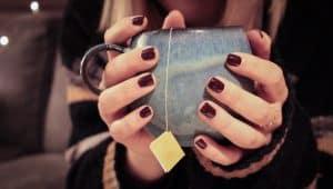 Teetasse mit Teebeutel in Händen gehalten