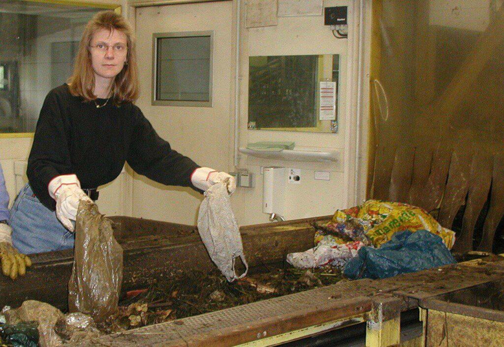 Frau hält falsch entsorgte Plastiktüten während der Handsortierung des Biomülls am Fließband in der Biokompostieranlage WGV Quarzbichl