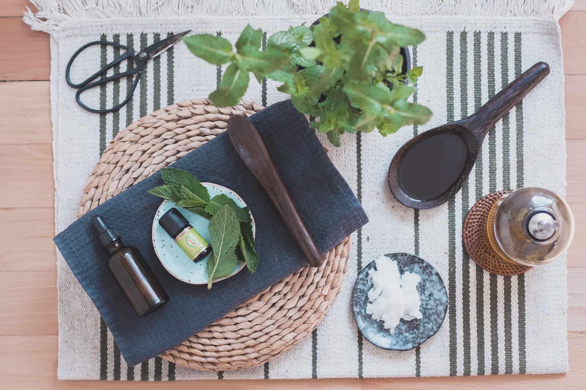 Kokosöl Olivenöl und Pfefferminzöl mit Minze und Schere auf Holzboden