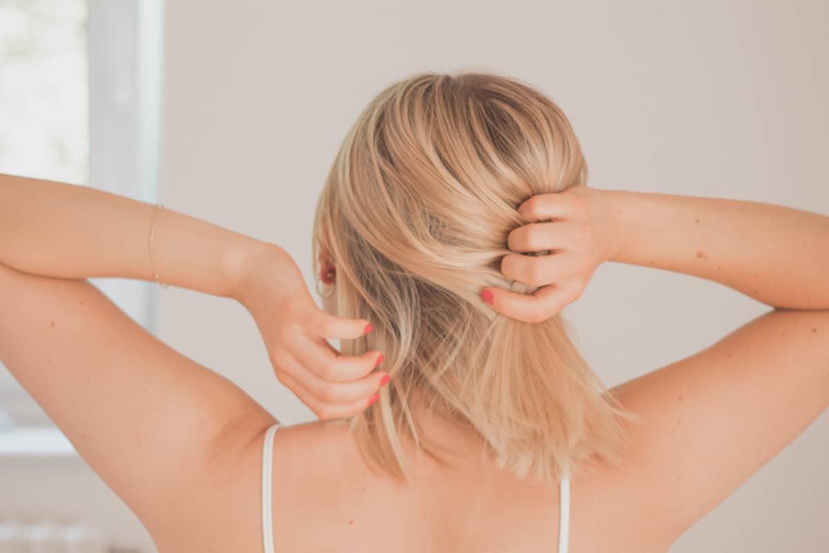 Blonde Frau fasst sich in Haare