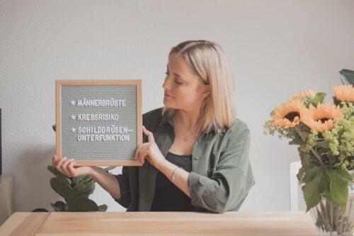 """Frau an Holztisch mit Sonnenblume und Letterboard mit Aufschrift """"Männerbrüste"""" """"Krebsrisiko"""" """"Schilddrüsenunterfunktion"""""""