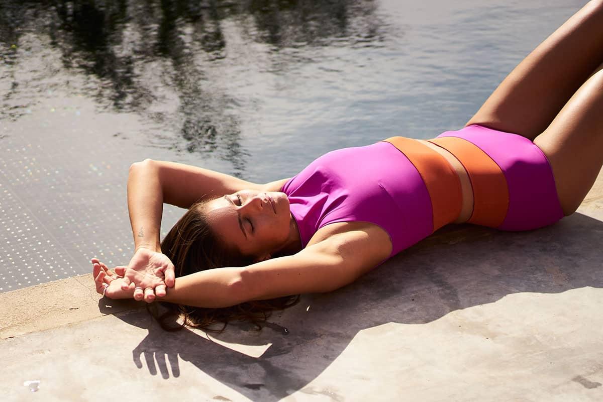 Frau liegend an Pool mit nachhaltiger Bademode aus Econyl von MyMarini Bikini in pink orange