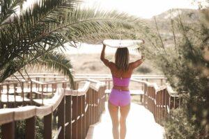Blonde Frau mit Surfbrett über dem Kopf und MyMarini Bikini in pink unter Palmen auf Holzsteg
