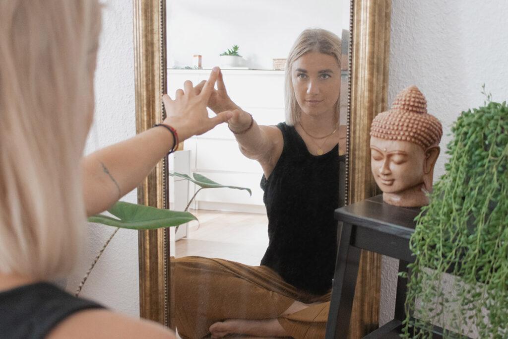 Frau schaut lächelnd in Spiegelbild und berührt mit Finger das Spiegelbild