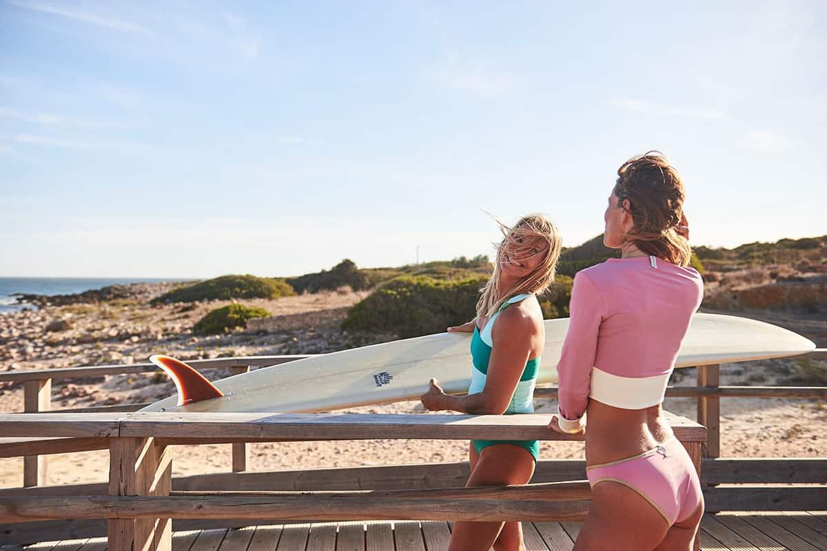 Frauen mit Surfbretter in Mymarini nachhaltiger Bademode aus Econyl auf Holzsteg