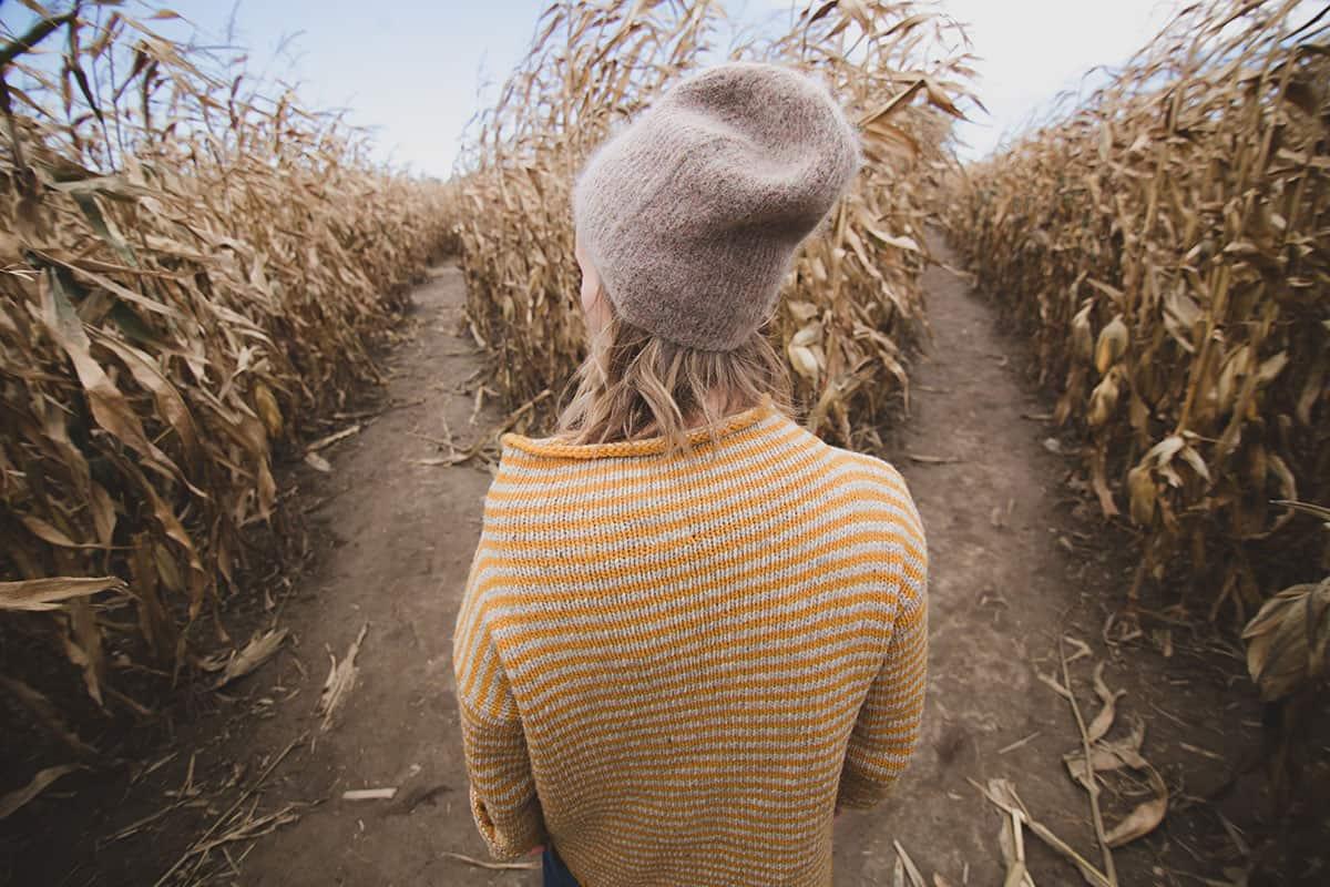 Frau mit Mütze in Maisfeld an Weggabelung