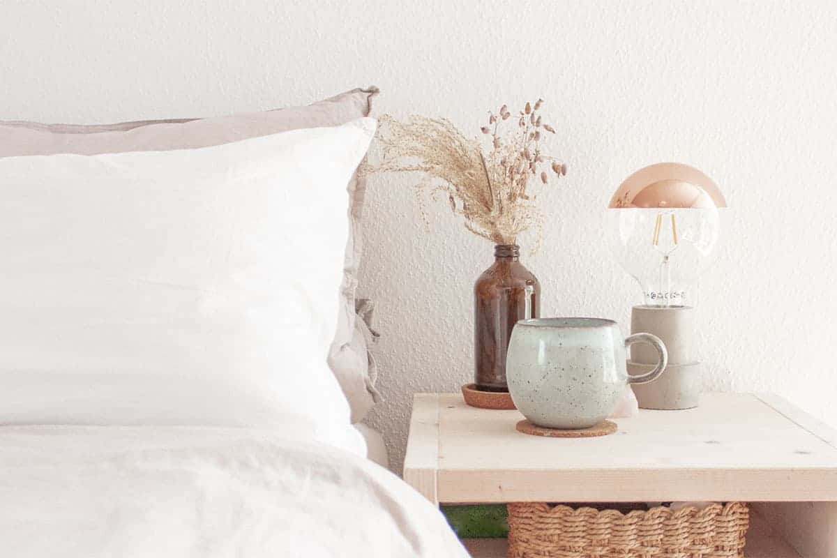 Weiße Bettwäsche und Nachttisch natürliches Holz Tasse auf Nachttisch