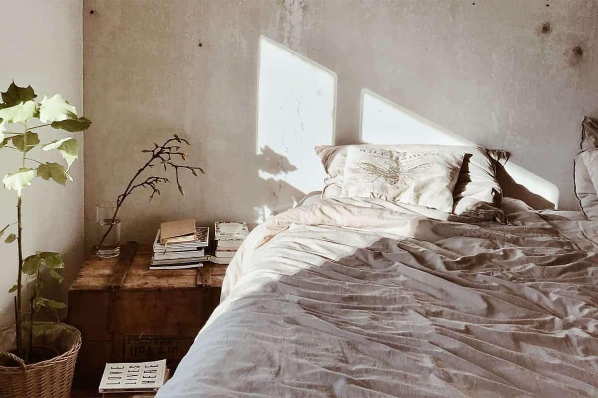 Gemütliches Bett mit grauer Bettwäsche im industrial Style neben Pflanzen und Holzkiste