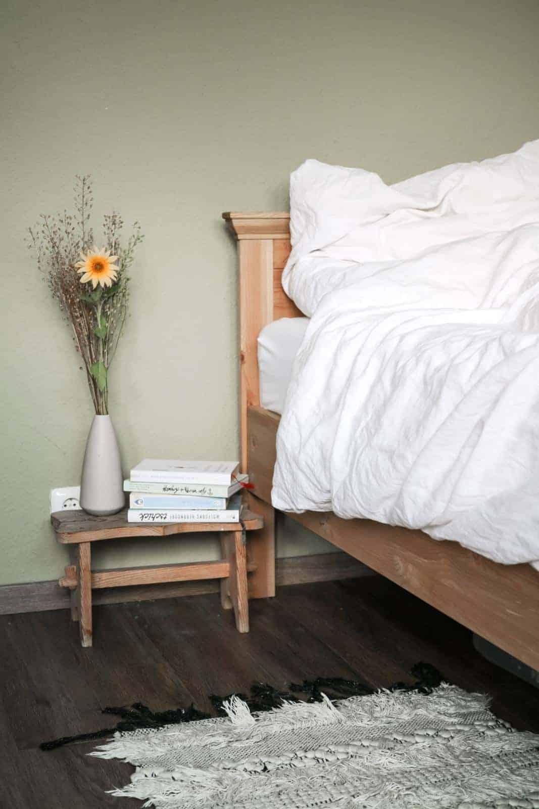 seit1832 nachhaltige Bettwäsche weiß neben Nachttisch mit Büchern